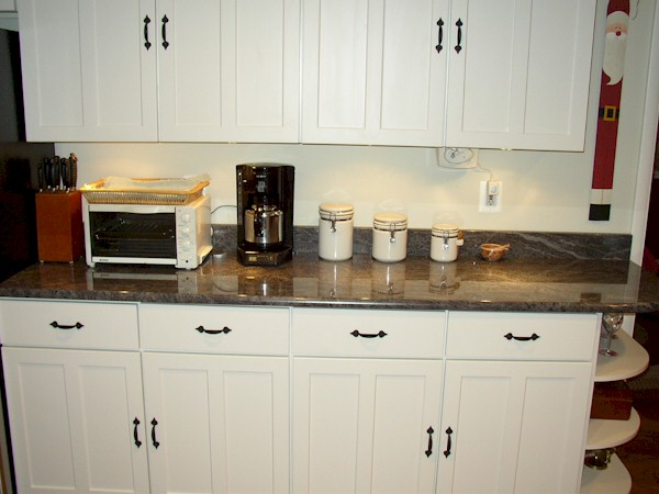 White maple cabinets with black iron pulls and rounded end shelf